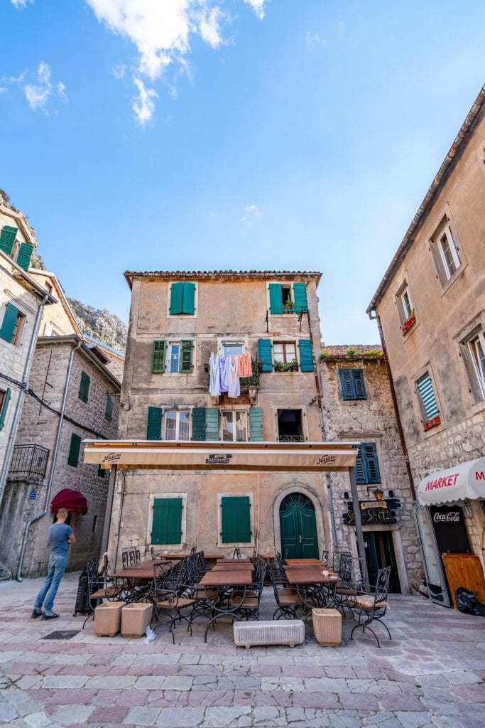 Tan Building with blue shutters and laundry hanging outside in Old Town of Kotor, Best Things to Do in Kotor Montenegro