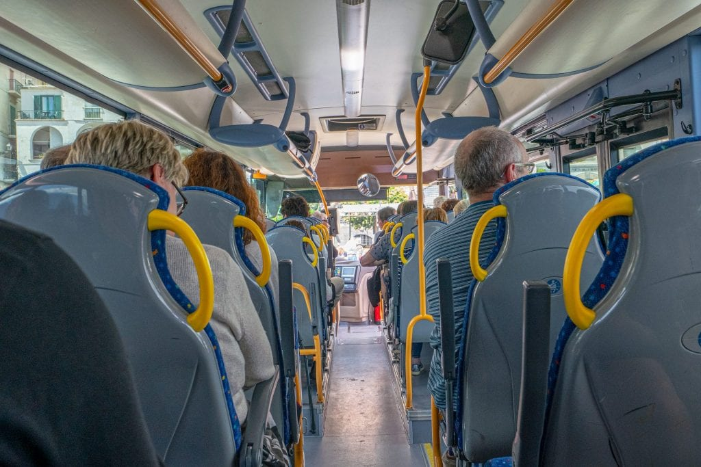 Photo of bus along the Amalfi Coast, with seats on each side and aisle in the middle. The bus is the cheapest, but not simplest, way of navigating your way through a 3 days on the Amalfi Coast.