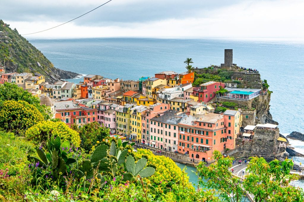 View of Vernazza starting to peek out with greenery in front as you approach the town from Monterosso al Mare--one of the best sections of trail for finding photo spots in Cinque Terre