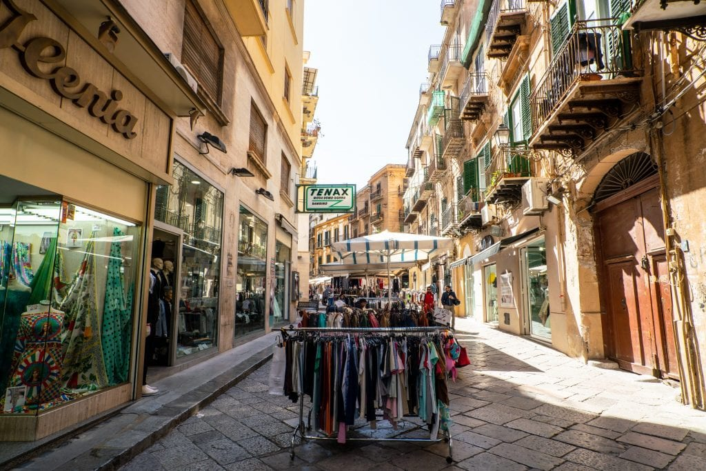 Street with racks of clothes for sale outside, Palermo Sicily