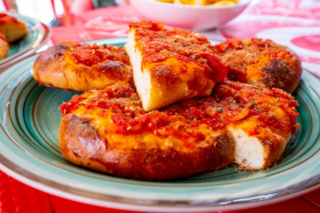 Sicilian pizza stacked on a green plate in Palermo