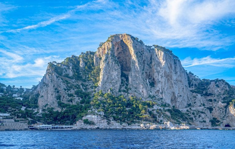 Photo of the island of Capri being approached by boat. You can see the sea at the bottom of the photo. Capri is an iconic destination to keep in mind when putting together your packing list for Europe summer!