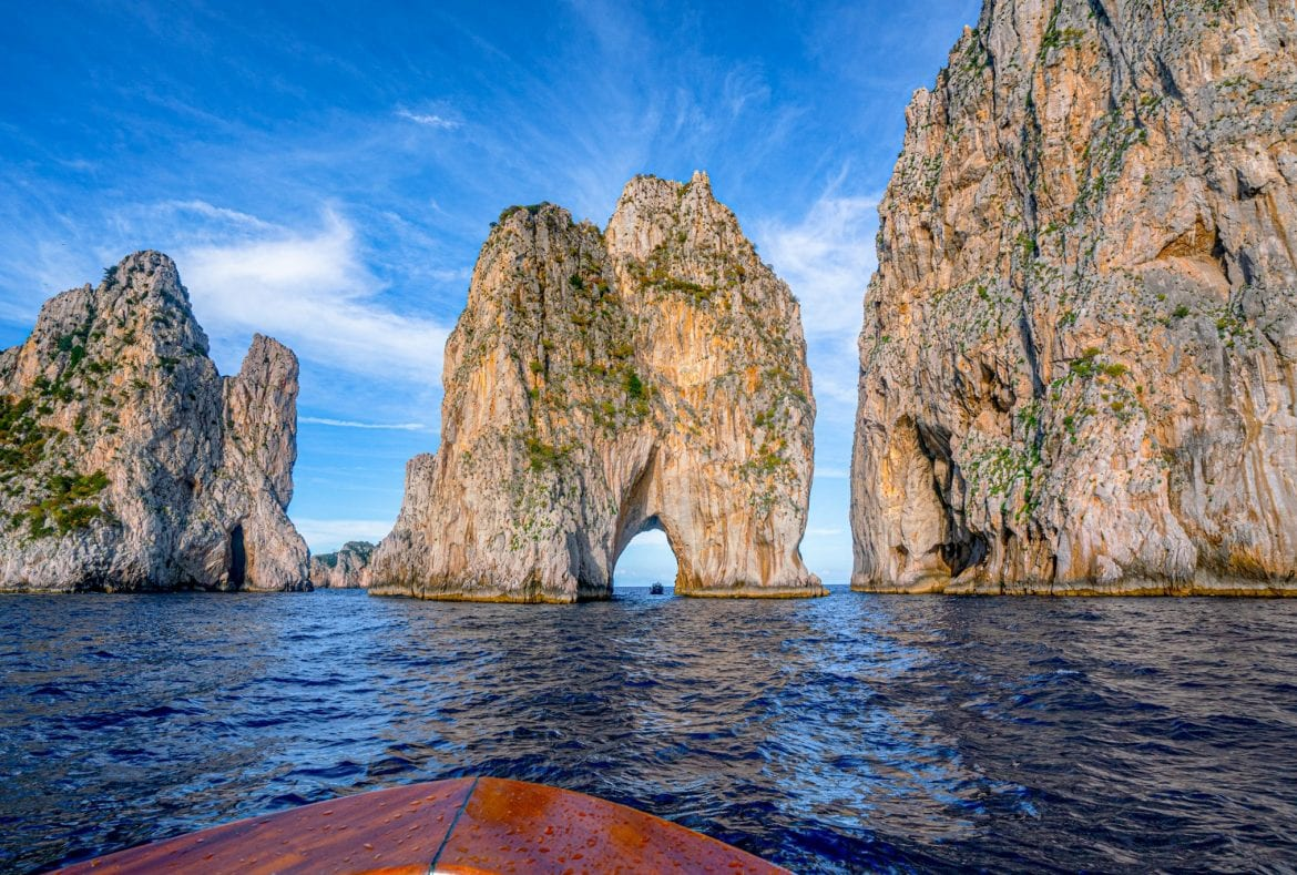 Faraglioni of Capri as seen from the water with the brown bow of a boat in the foreground. Capri is one of the most romantic places in Italy, partially because of the legend of the Faraglioni!