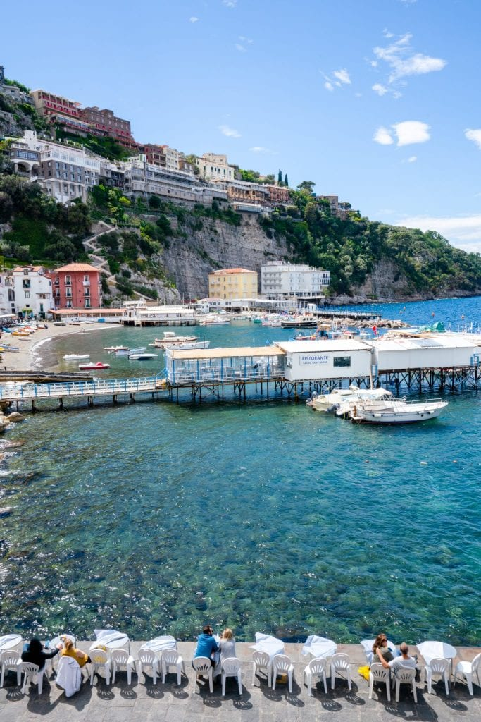 View of Marina Piccola, Sorrento, with white tables with people eating at them in the foreground. If you have extra time for your Amalfi Coast itinerary, be sure to see Sorrento.