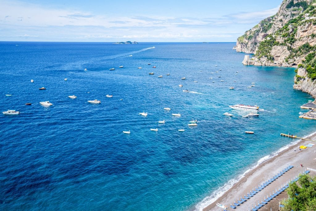 Water surrounding Amalfi Coast with boats on the water. There's a small piece of Positano's Beach visible in the bottom righthand corner of the photo.