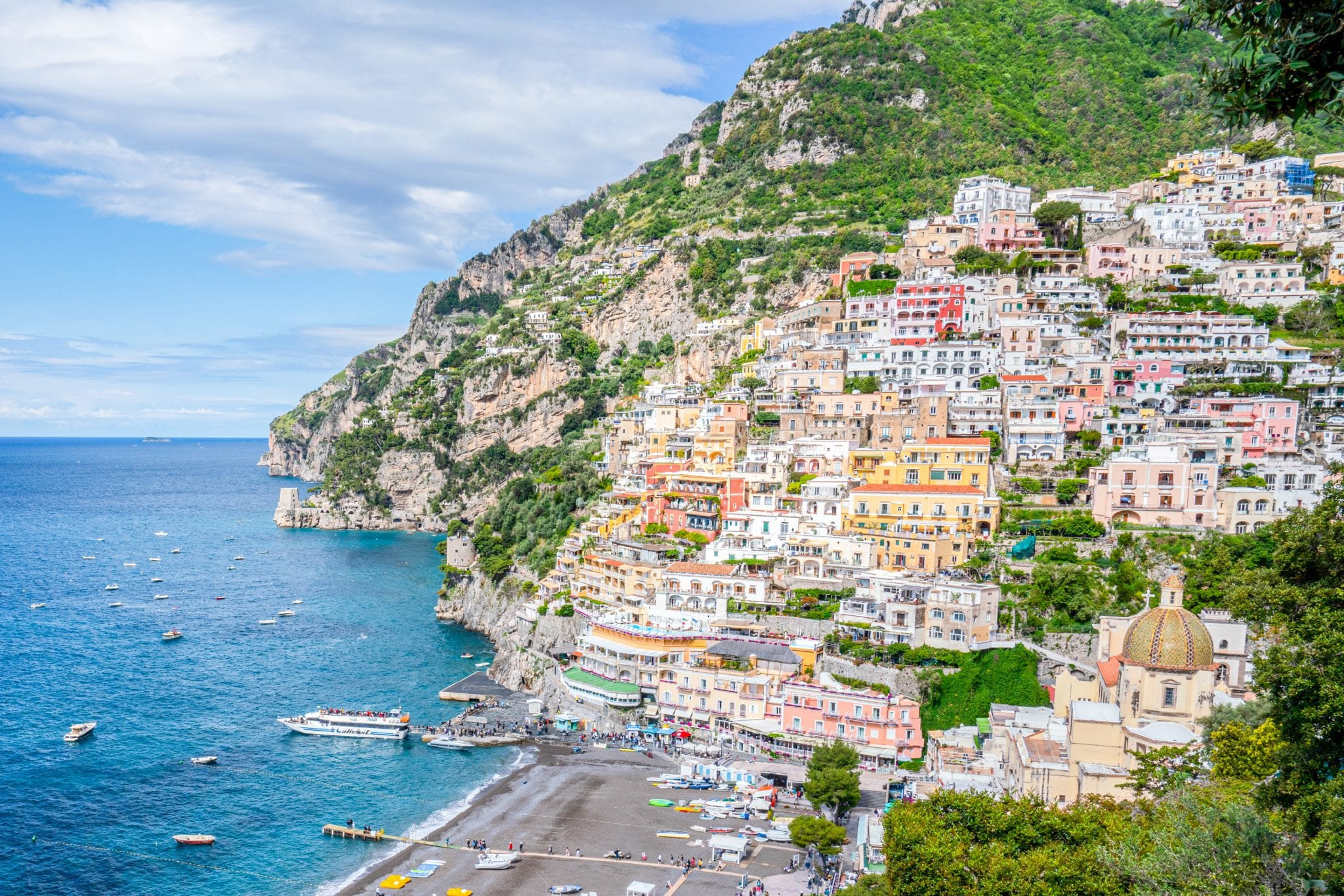 Photo of Positano from above. The town and cliff is on the right, beach at center bottom, and sea with boats to the left. Recommended stop on a 3 day Amalfi Coast itinerary.