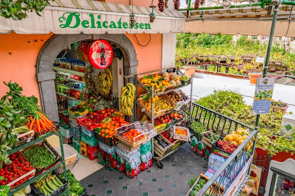 "Fruit stand in Positano as shot from above. An overhang says ""Delicatesen"" in green letters and a coca-cola sign hangs below that."