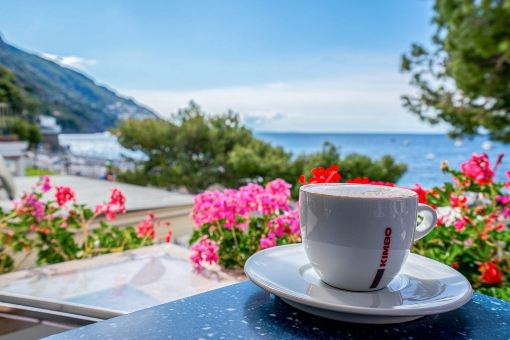 View of pink and red flowers with Positano beach in the background and cup of coffee on a white saucer in the foreground.