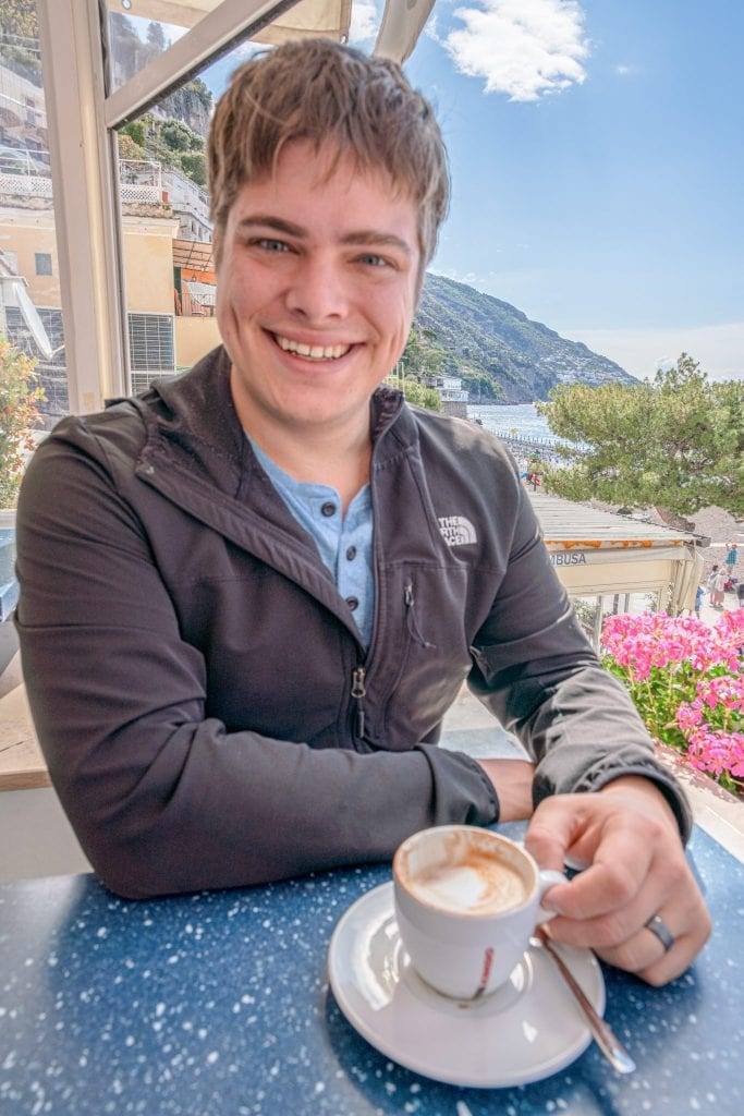 Man drinking a cup of coffee in Positano along the Amalfi Coast, Italy