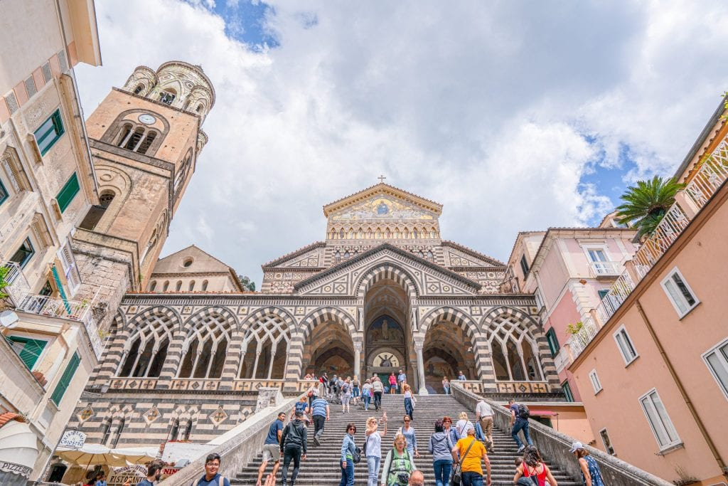 Facade of Duomo in Amalfi Town with crowd on the steps in the foreground.