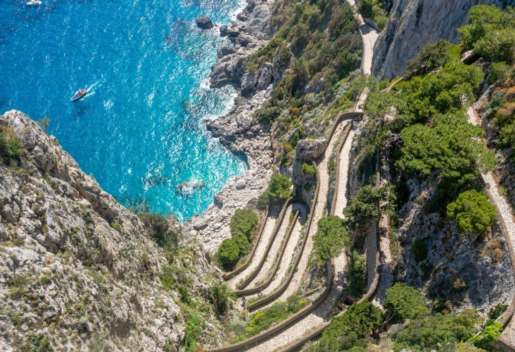 Photo of a winding road on Capri shot from above. You can see cliffs in the bottom of the photo and bright blue sea in the upper left.