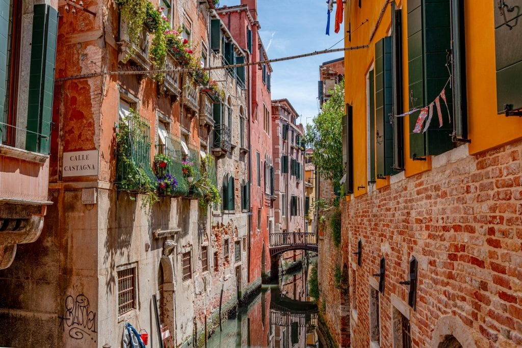 Small canal in Venice on a sunny day, lined by windows with flowerboxes