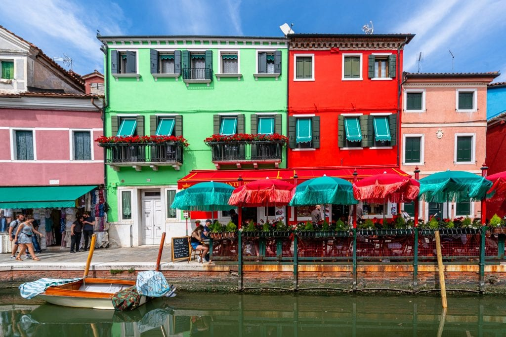 Photo of colorful houses in Venice with umbrellas and a canal out front.