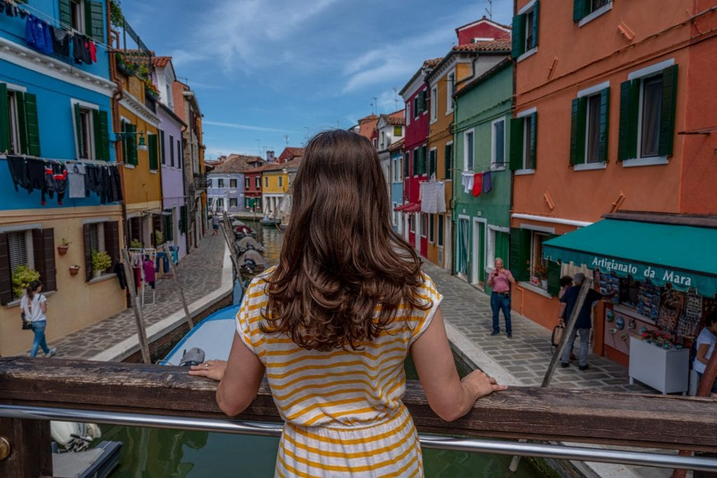 Girl standing on a bridge in front of a canal in Burano