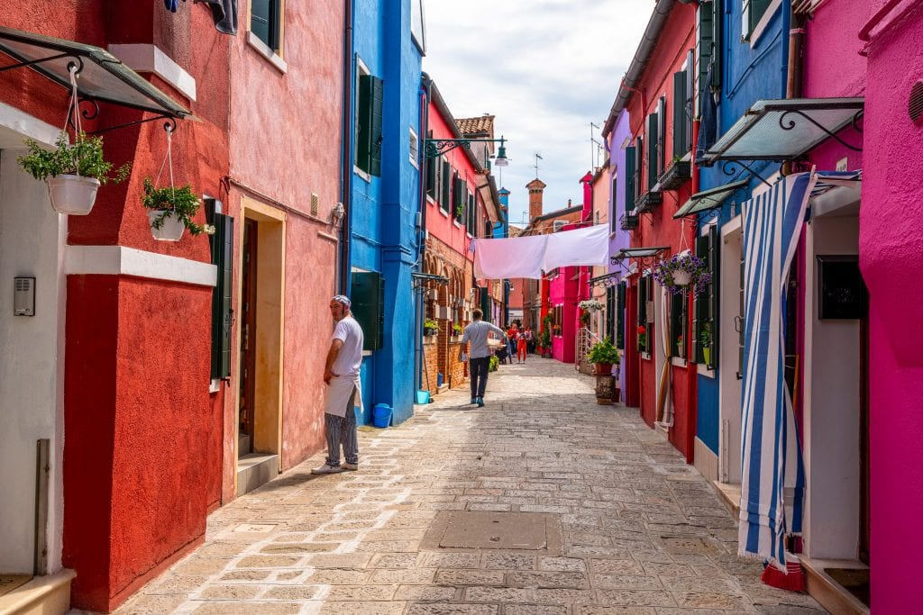 Photo of a colorful street in Burano with a man standing to the left, as seen on a trip to Burano from Venice.