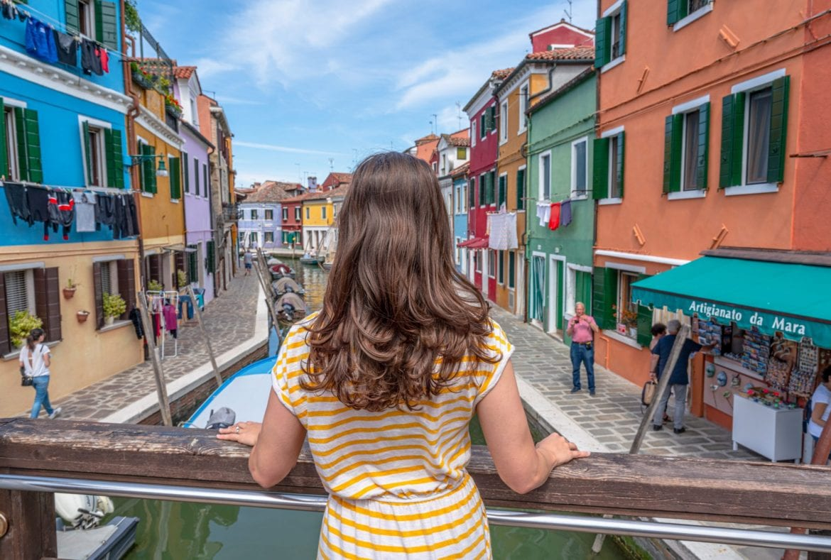Photo of woman overlooking colorful houses of Burano from a bridge on a day trip from Venice to Burano.