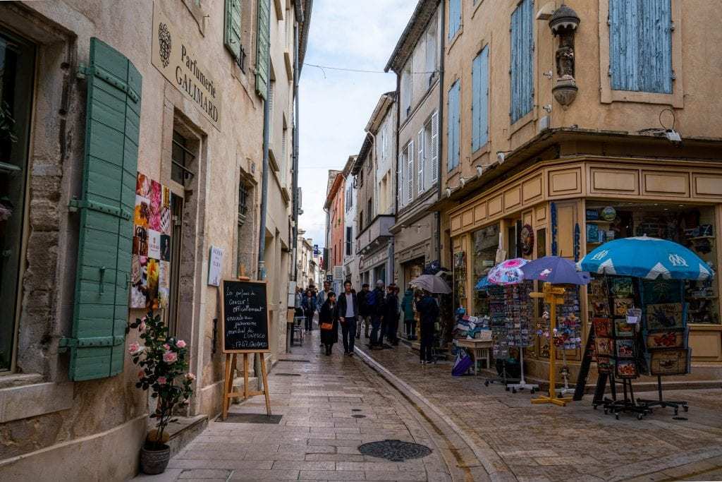Pedestrian street in Saint-Remy-de-Provence France, framed by buildings with colorful shutters on either side.