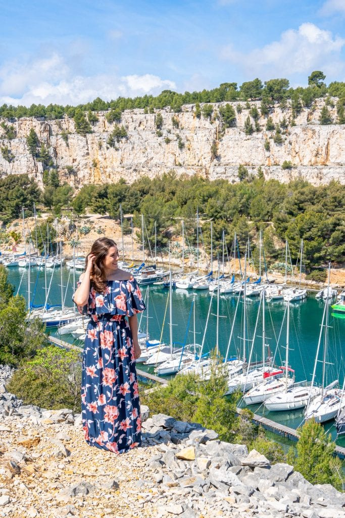 Woman in floral dress standing in front of Port Miou near Cassis Provence France