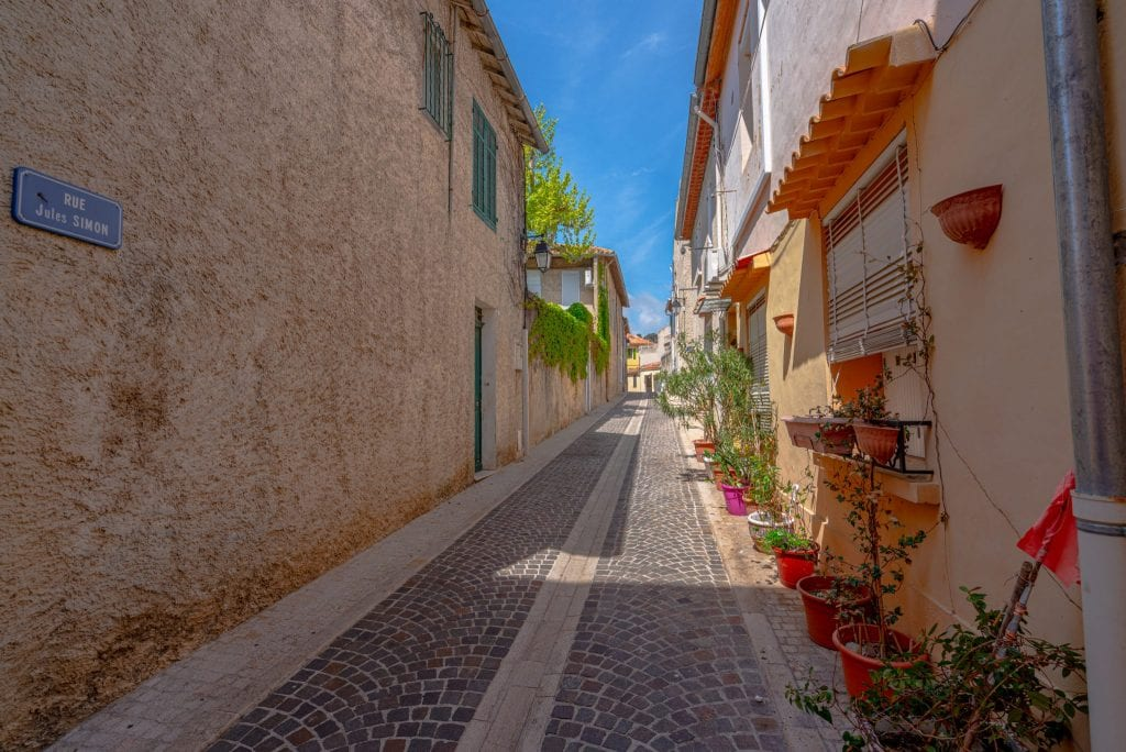 Empty pedestrian street in Cassis France. There's a blue street sign on the left side of the photo and red flowers on the right.