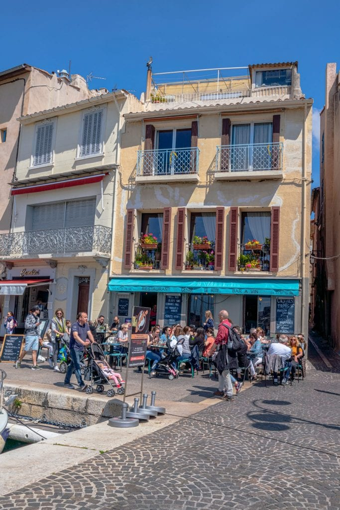 Busy restaurant in Port de Cassis with diners sitting at tables on the sidewalk
