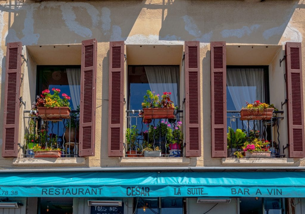 3 windows with red shutters and a turquoise banner underneath them in Cassis France