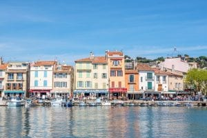 Buildings in front of harbor of Cassis France, their reflections are on the water in the bottom half of the photo.