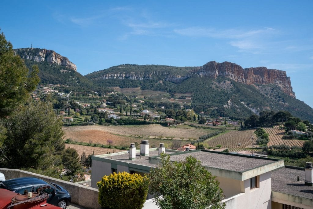 Countryside near Cassis France, with rooftops in the foreground and vineyards and cliffs in the background.