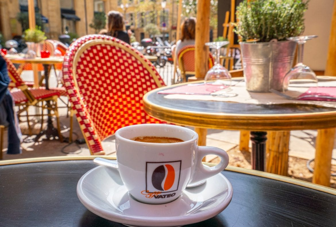 Cup of coffee sitting on a black table outdoors during a typical French breakfast in France, with a red chair in the background