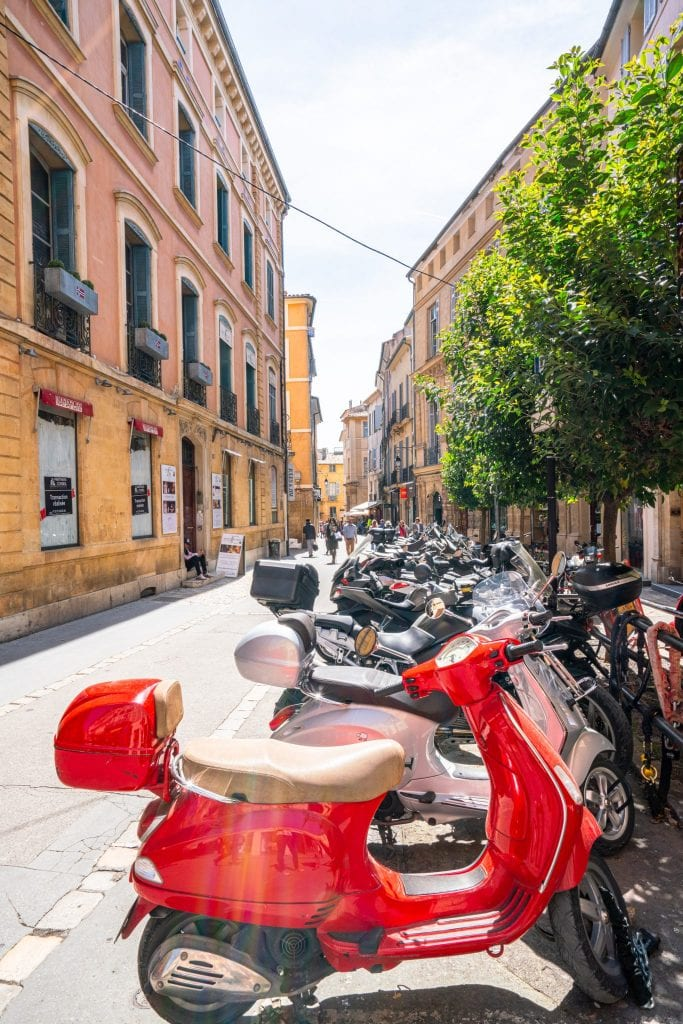Street in Aix-en-Provence with a red Vespa in the foreground and a yellow building in the background