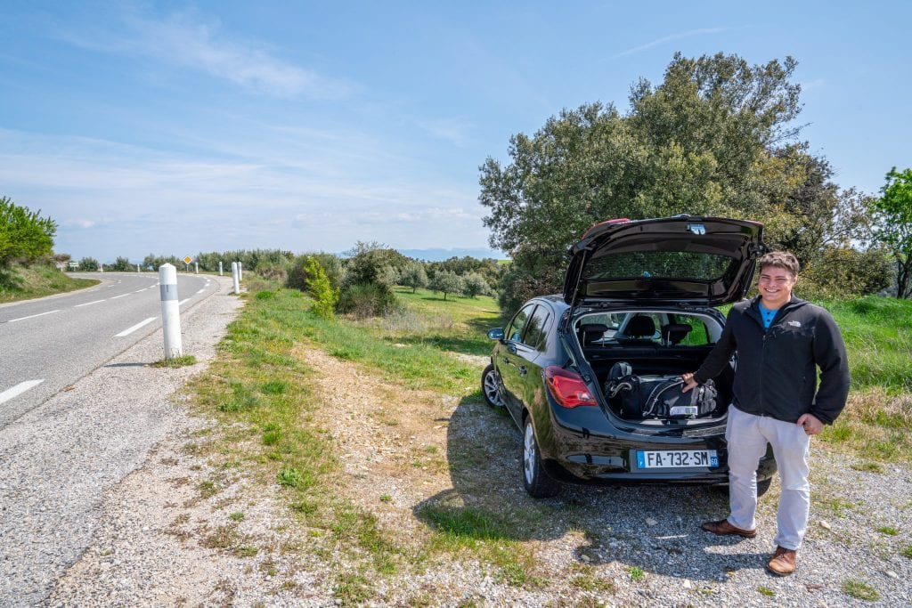Jeremy standing to the right of a country road during our road trip in France. He's standing in front of a black rental car with the rear hatch open, and he's wearing a black jacket.