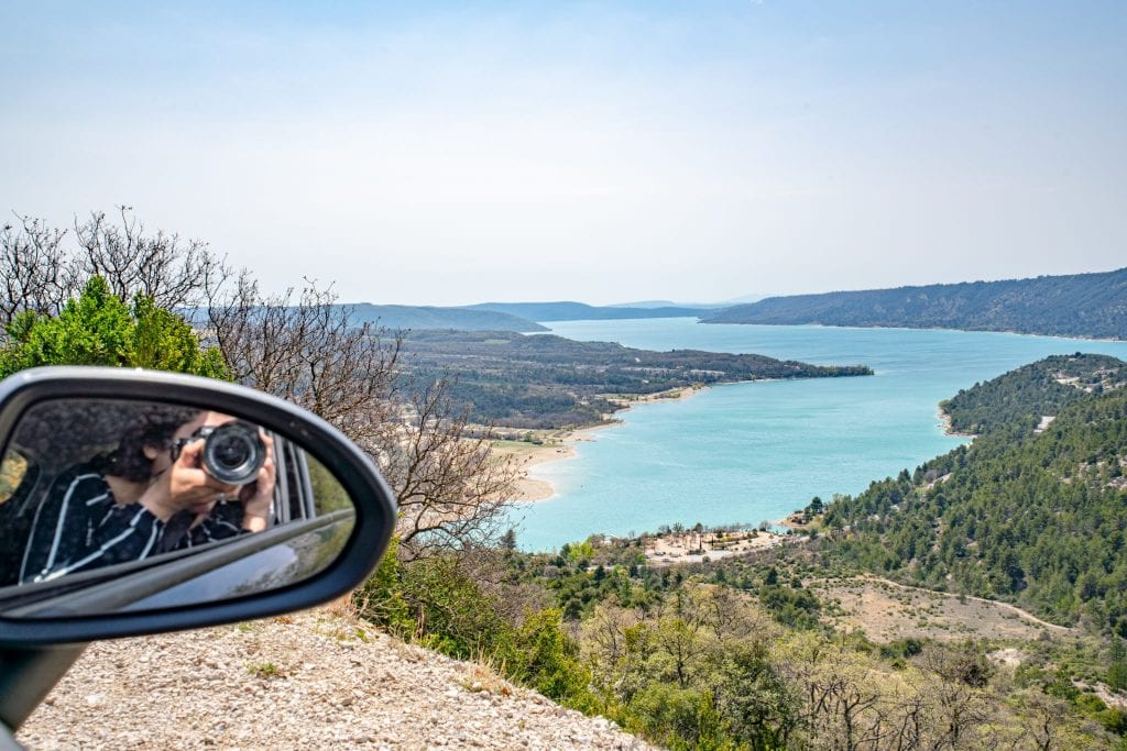 Photo of Lake Sainte-Croix with Kate visible snapping a photo in the rearview mirror on the left--a camera for photos like this definitely belongs on your road trip packing list!
