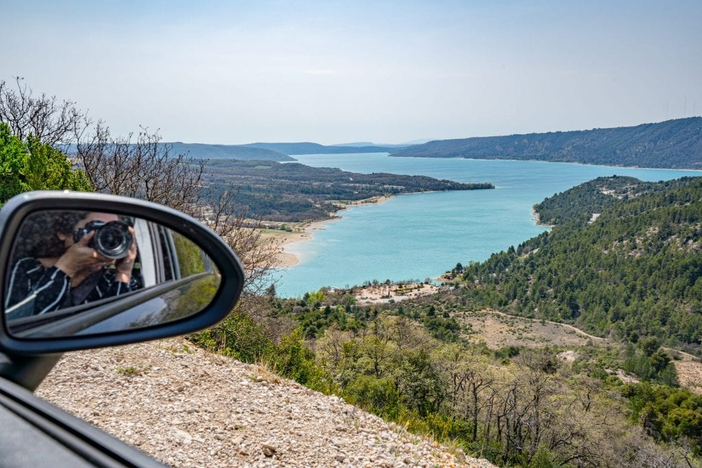 Photo of Lake Sainte-Croix as seen while driving in France. You can see Kate holding a camera to her face reflected in the rearview mirror of our rental car on the left side of the photo