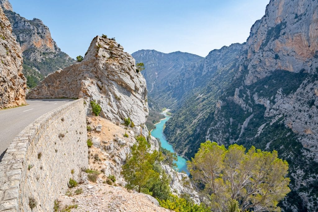 Photo of an empty road to the left with Verdon Gorge visible on the right--be sure you have the perfect road trip packing list ready to go before seeking out amazing views like this!