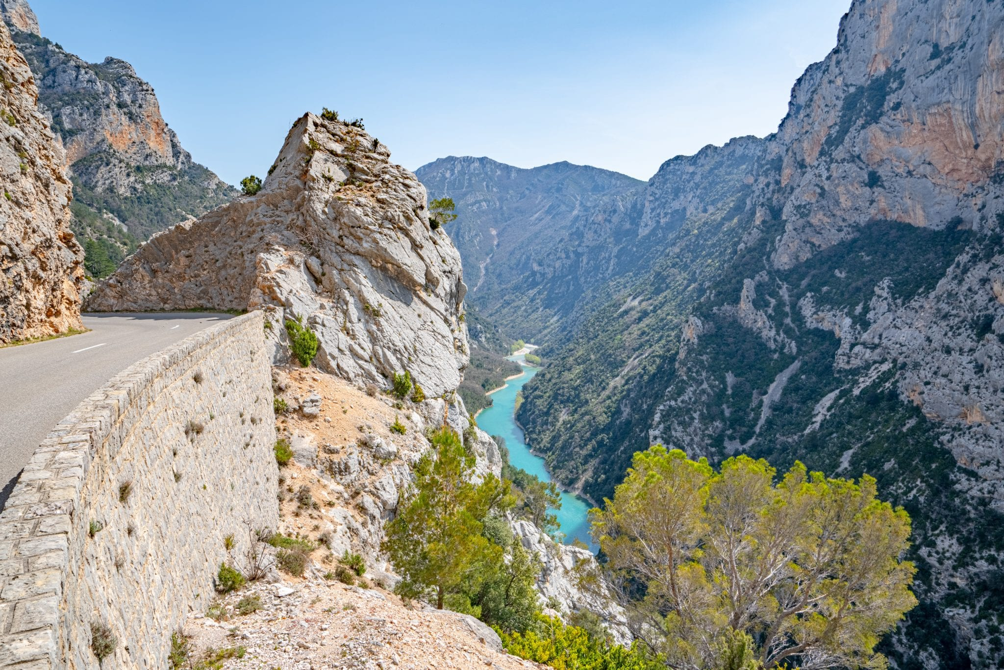 Photo of an empty road on the left, with the Verdon Gorge to the right. The turquoise river of the gorge is visible in the center of the photo. Definitely worth stopping here on a France road trip!