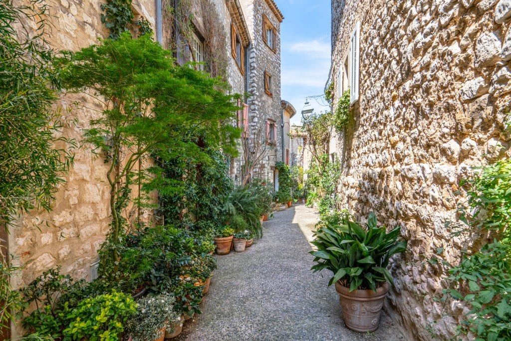 Photo of a cobblestone street in Saint-Paul-de-Vence France, with stone buildings on either side and green plants along the street--don't miss this stop during your south of France itinerary!