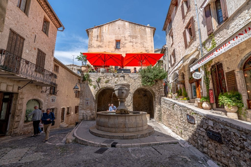 Photo of a square in Saint-Paul-de-Vence France--there's a red banner hanging over a restaurant in the center of the photo.