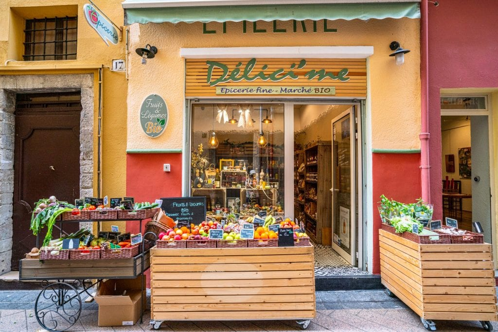 Deli in Nice France with a car full of fruits and vegetables parked in front of it.