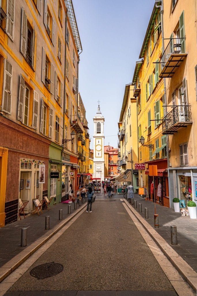Colorful street in Nice, France, with yellow buildings on both sides.