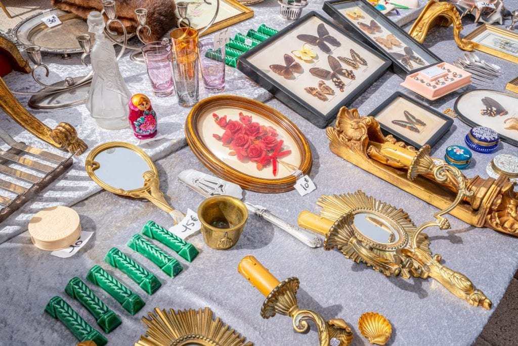 Collection of antique items for sale, laid out on a table at a market in Nice, as seen during a south of France vacation.