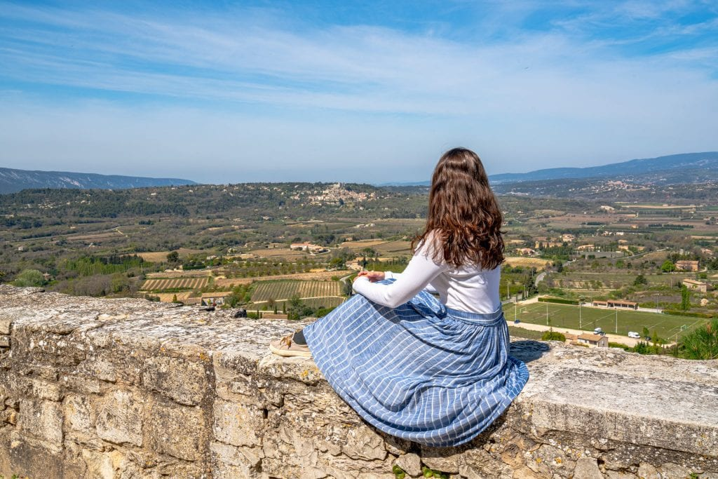 Kate in a blue skirt sitting on a stone wall overlooking the countryside of the Luberon Valley. Taken in Bonnieux France.
