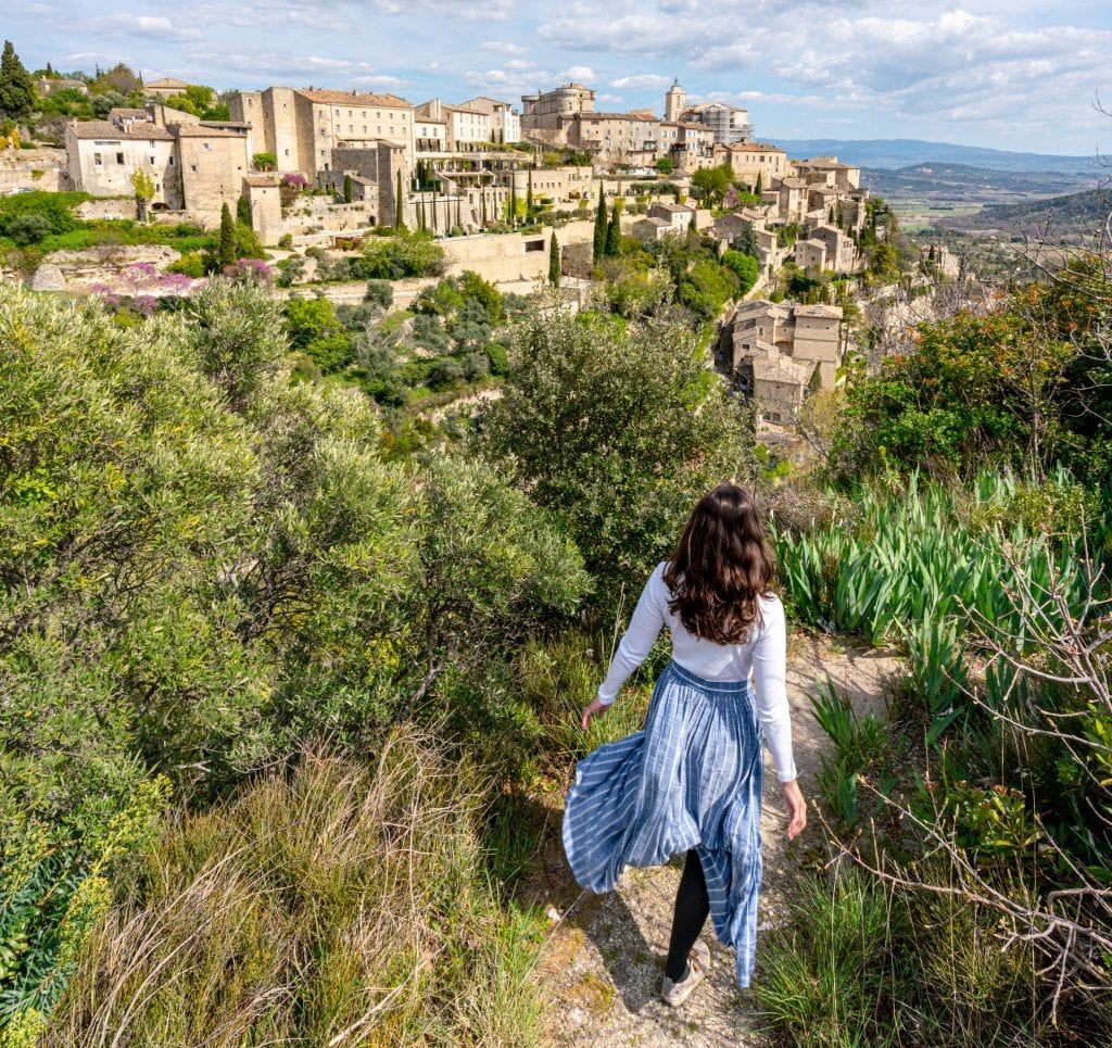 Kate in a blue skirt on a ledge overlooking Gordes, one of the best places to visit in the South of France