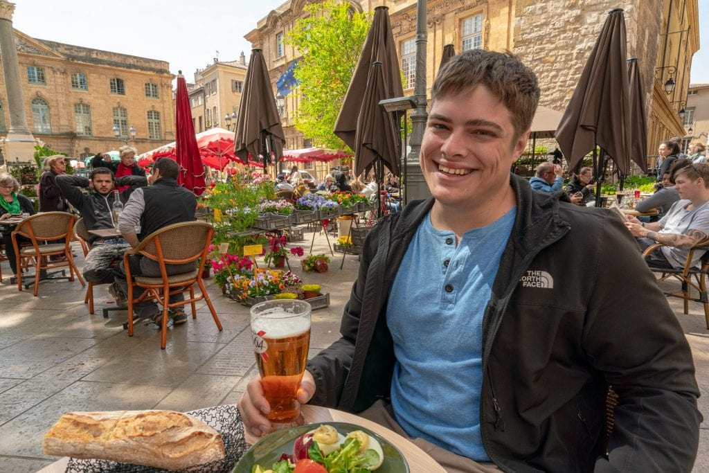 Jeremy in a blue shirt and black jacket, holding a beer while eating lunch in a square of Aix-en-Provence