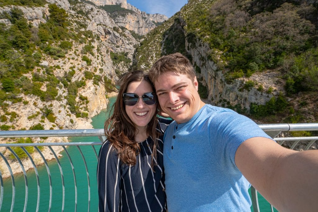 Selfie of Kate and Jeremy in front of the Verdon Gorge. Both are wearing blue shirts and Kate is wearing sunglasses.
