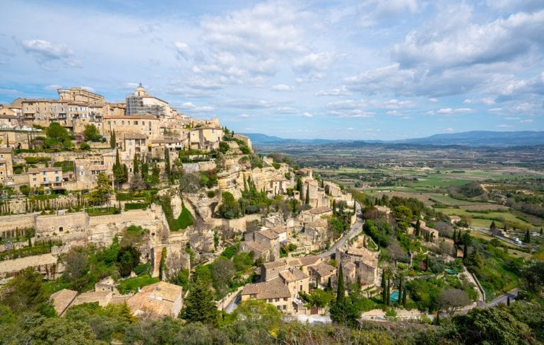 Photo of the village of Gordes France taken from above. The village is visible on the left and countryside on the right. Gordes is considered one of the best places to visit in the south of France!