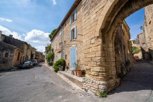 Street in Goult France with a stone building framed with blue shutters on the right