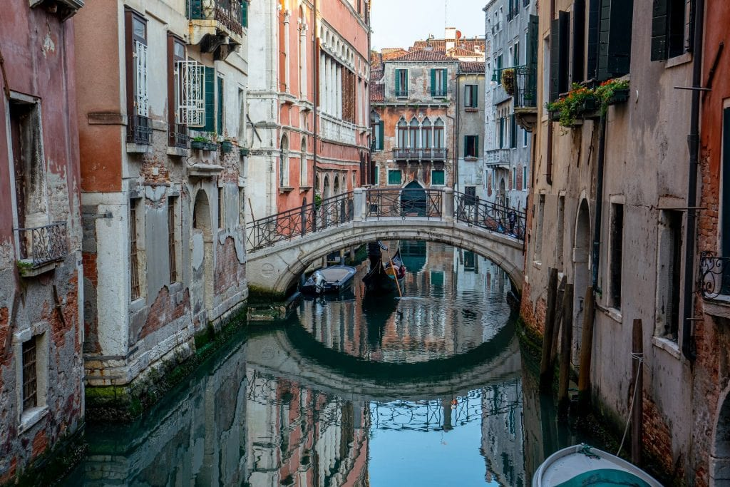 Footbridge reflecting into a quiet canal in Venice. Venice is a fascinating city and home to some very interesting facts about Italy