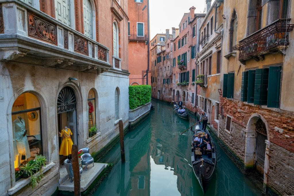 Photo of 2 gondolas in a small canal in Venice.