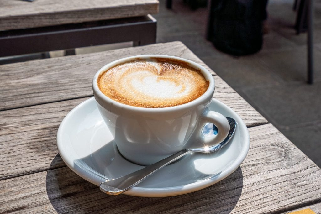 Cappuccino on a plate with a spoon next to it on a wooden table bathed in sunlight. Excellent Italy travel tip: start every morning with one of these!