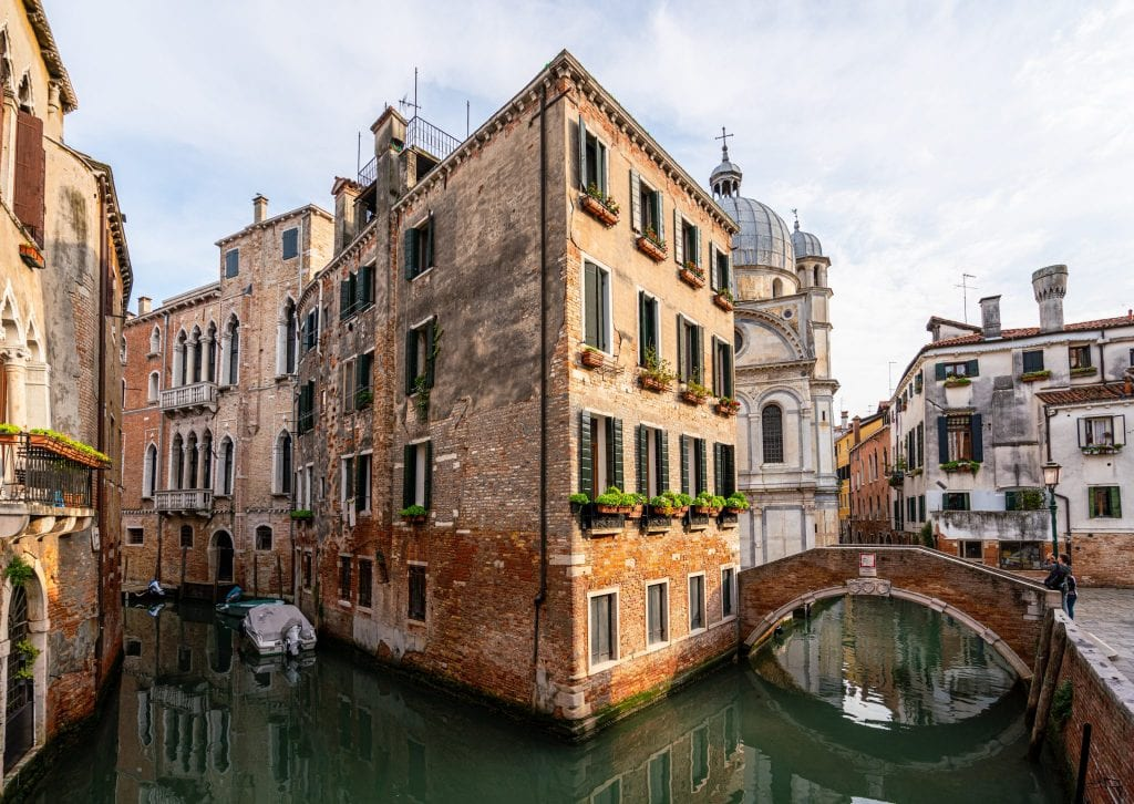 Canal in Venice, with a view of a bridge on the right.