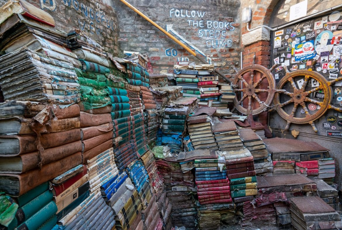 Staircase of books at Libreria Acqua Alta in Venice as seen from the side, two ship's wheels are propped up on the righthand side.